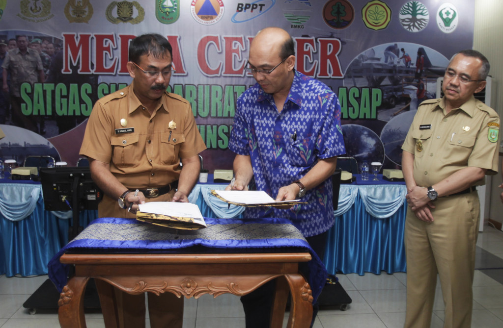 Riau Andalan Pulp and Paper (RAPP) Director Mulia Nauli (center), signs a Memorandum of Understanding with the Riau Regional Disaster Mitigation Agency at Roesmin Nurjadin military airbase in Pekanbaru, Riau, on June 26. The signing ceremony was witnessed by Riau Deputy Governor Arsyad Juliandi Rachman (right) and Said Saqlul Amri, head of the Riau Province Disaster Mitigation Agency (left). (GA Photo/A.A. Kresna)