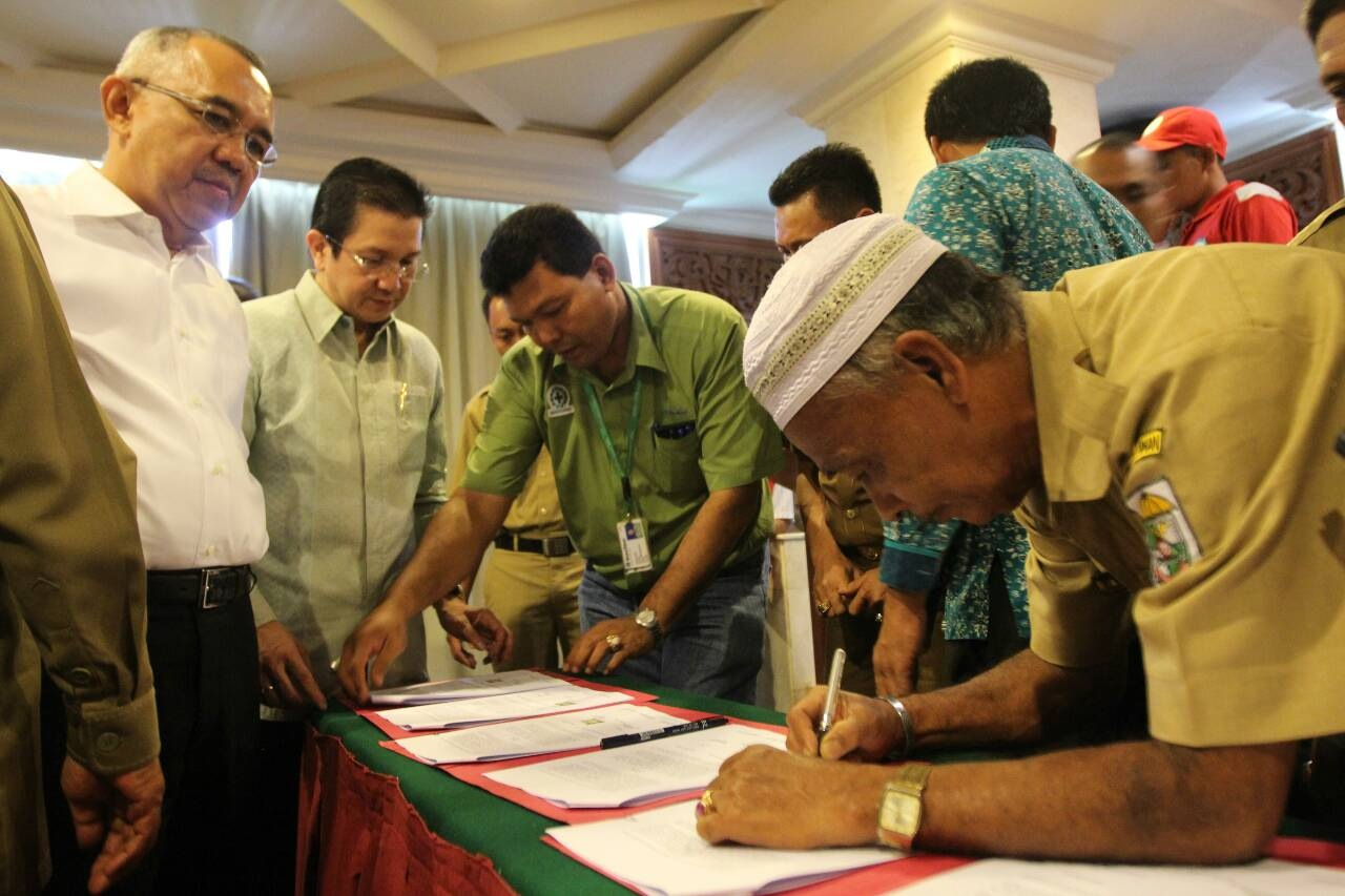 Yunus, Sering village chief, signs a cooperation agreement alongside 8 other villages, reaffirming their participation in the Fire Free Village Programme, witnessed by Riau Interim Governor Arsyadjuliandi Rachman and APRIL MD, Tony Wenas